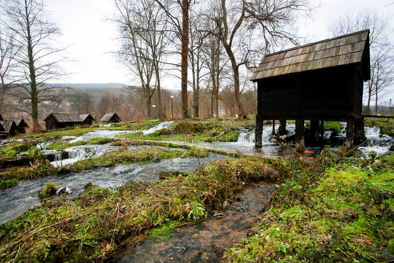 Винтажная деревянная водяная мельница стоит на быстром пропуская реке в старой деревне около города Jajce в Босния и Герцеговина стоковое фото rf