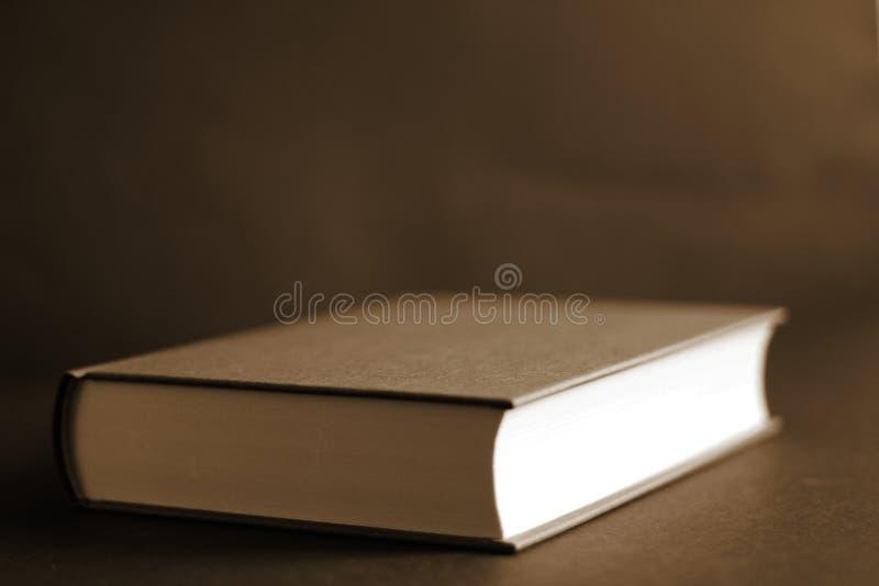 Винтажная закрытая коричневая книга, коричневая предпосылка, взгляд со стороны, стоковое изображение rf