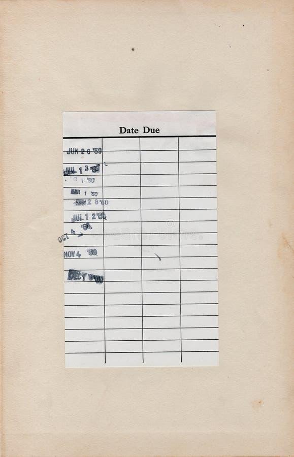 Винтажная карточка срока оплаты библиотеки прикрепленная к пожелтетой странице книги стоковое фото
