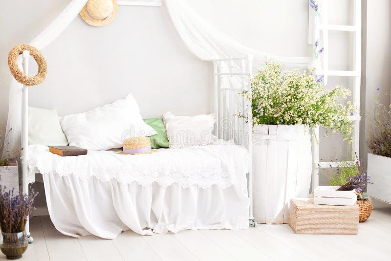 Винтажная квартира-студия внутренняя в светлых цветах в старом стиле Затрапезный белый шикарный интерьер спальни для загородного  стоковое фото rf