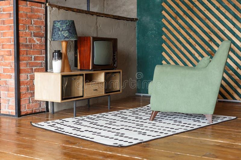 Винтажная комната с ковром, старомодным креслом, ретро ТВ, стойкой ТВ, вазой и стандартной лампой Ретро интерьер стоковая фотография rf