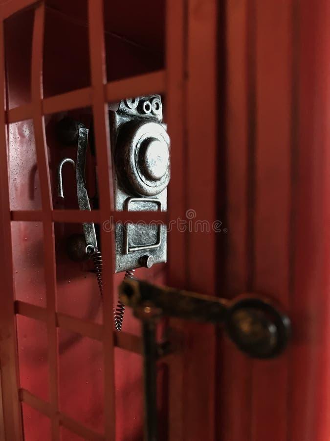 Винтажная красная переговорная будка с постаретым ретро телефоном шкалы смертной казни через повешение стены внутрь Старомодное у стоковая фотография rf