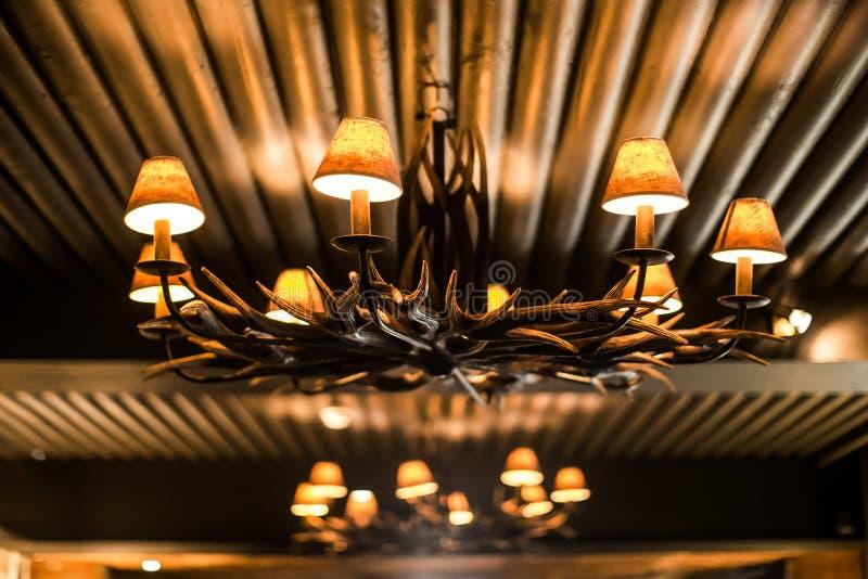 Винтажная люстра с antlers и желтыми лампами стоковые фото
