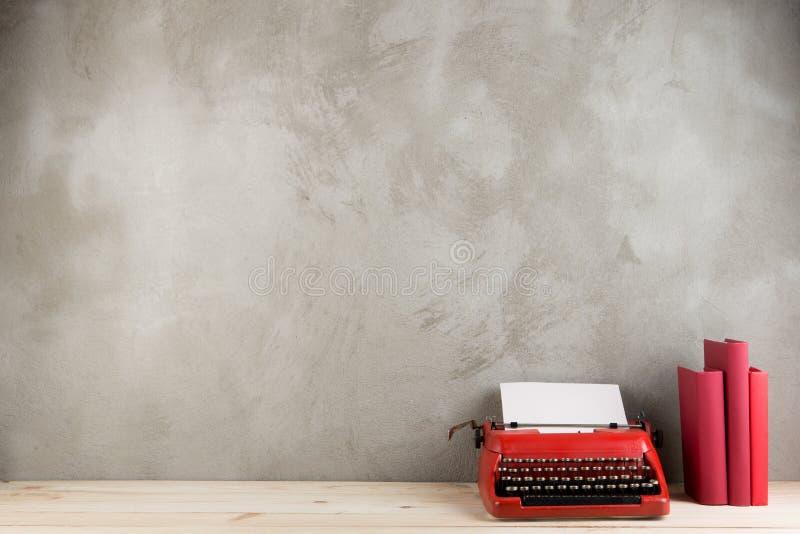 винтажная машинка и книги на таблице с чистым листом бумаги на деревянном столе стоковые изображения rf