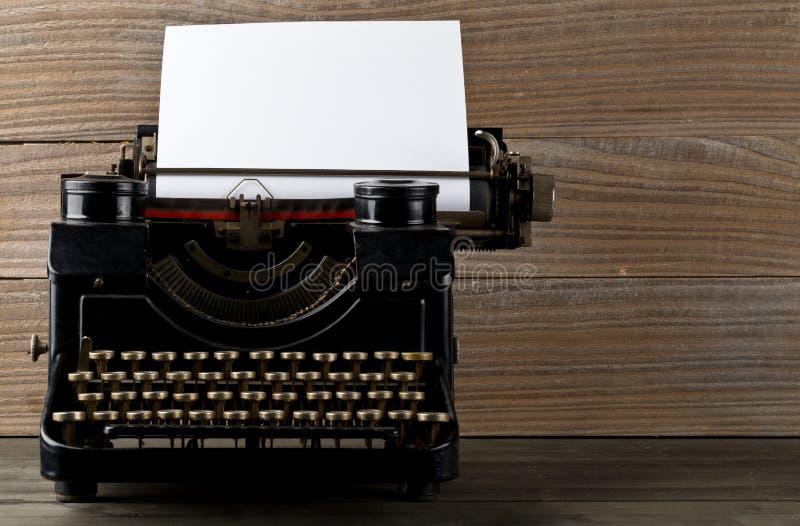 Винтажная машинка с пустой, чистый лист бумаги на деревянном tabl стоковое фото
