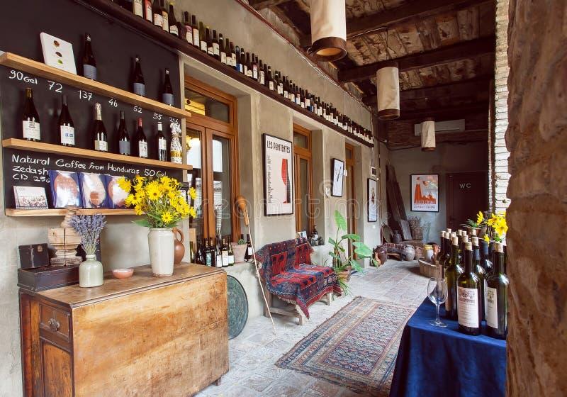 Винтажная мебель и много бутылок вина внутри ресторана в старом здании в грузинском стиле стоковые фотографии rf