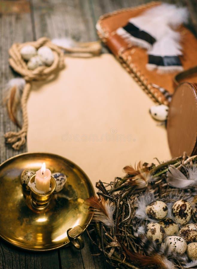Винтажная насмешка вертикали вверх на деревенской деревянной доске Подсвечник и яичка крупного плана внутри меньшей корзины на ли стоковые фотографии rf