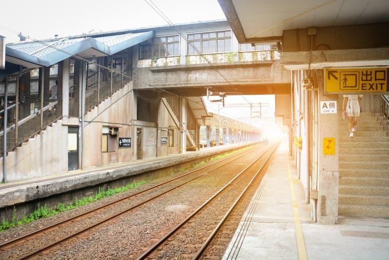 Винтажная платформа поезда, железнодорожный вокзал, здание для пересекая железнодорожных путей с предпосылкой захода солнца, Тайв стоковое изображение