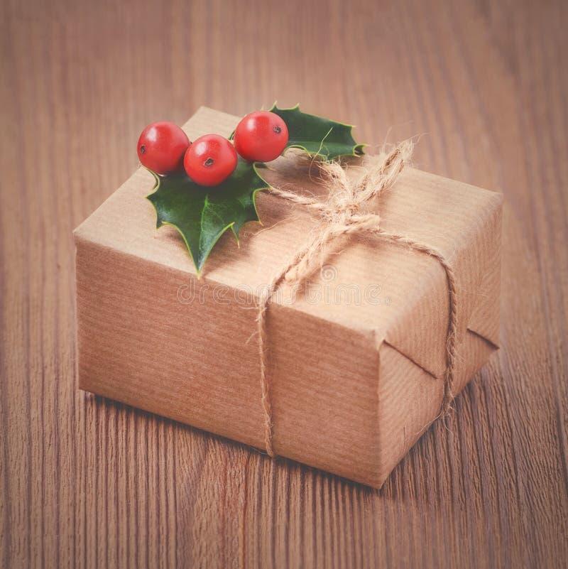 Винтажная подарочная коробка, бумага kraft, веревочка и ягоды падуба на старое деревянном стоковые фото