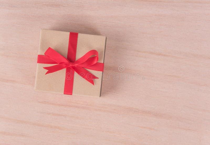 Винтажная подарочная коробка с красной лентой на деревянной предпосылке congratul стоковые изображения