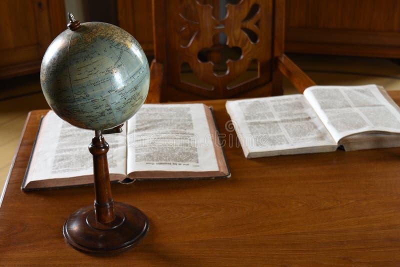 Винтажная ретро таблица с глобусом и книгами стоковые фотографии rf