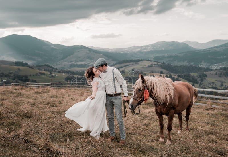 Винтажная свадьба жениха и невеста на ранчо с лошадью на пиковых холмах стоковая фотография rf