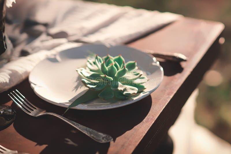 Винтажная сервировка стола с цветком на плите на деревянном столе Украшение свадьбы загородного стиля стоковые фото