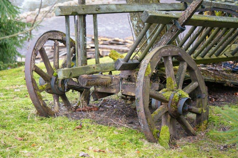 Винтажная тележка повреждено античный переход Ретро тележка стоя на лужайке Dray в траве старо стоковые изображения rf