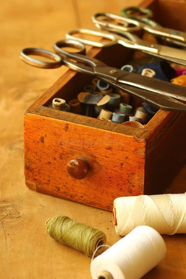 Винтажная шить коробка с ножницами и катышками потока на таблице с отверстием червя стоковые фото