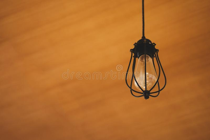 Винтажная электрическая лампочка Edison вися сверх против деревянной предпосылки стоковое изображение