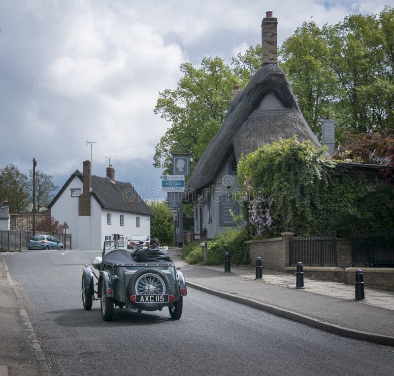 Винтажное вождение автомобиля через деревню стоковое фото rf