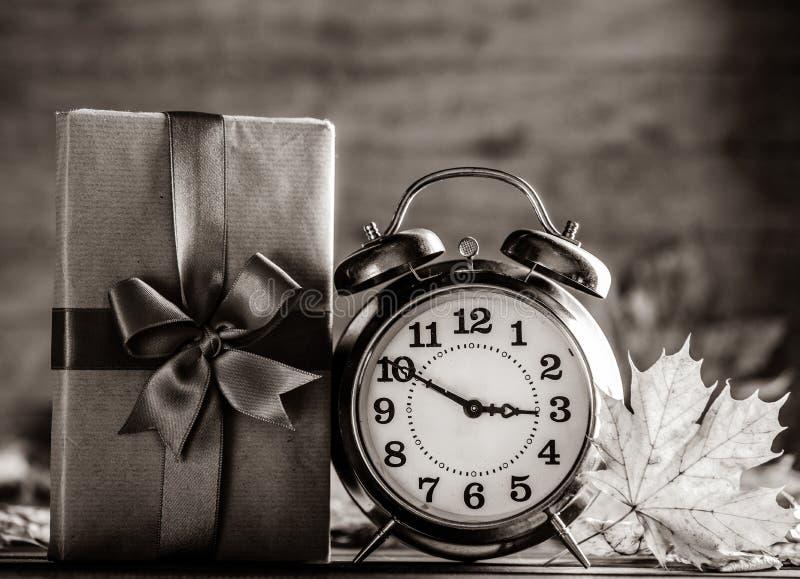 Винтажное дерево будильника и клена выходит с подарочной коробкой стоковая фотография rf