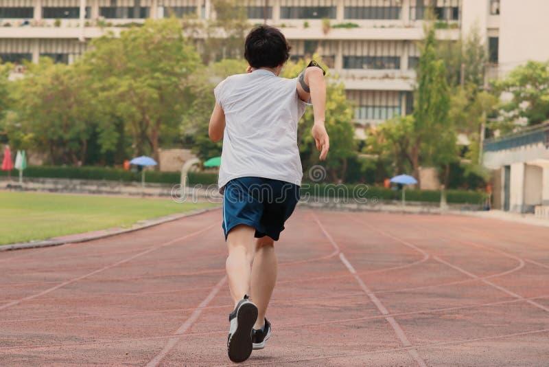 Винтажное изображение фильтра заднего взгляда молодого азиатского спринтера выходя начинать на беговую дорожку на стадионе атлети стоковые фотографии rf