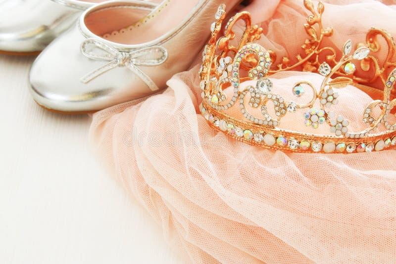 Винтажное платье Тюль розовое шифоновое, крона и ботинки серебра на деревянном белом поле стоковые изображения