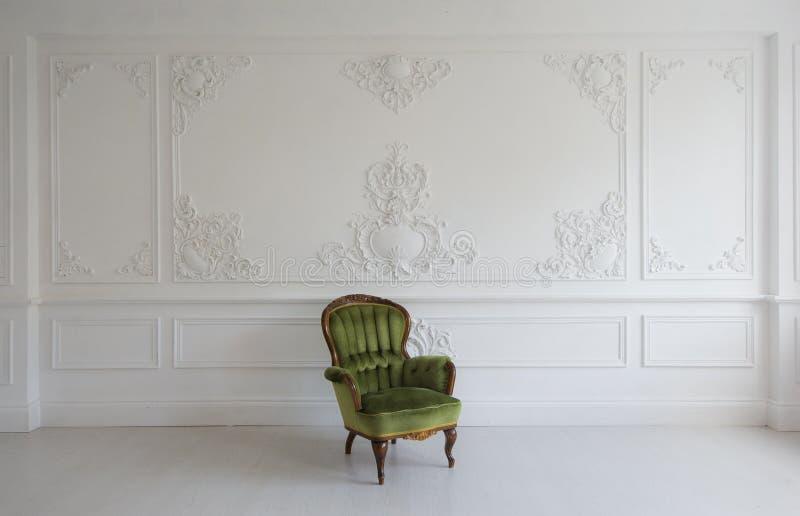 Винтажное роскошное зеленое кресло в белой комнате над элементами roccoco прессформ штукатурки барельеф дизайна стены стоковая фотография rf