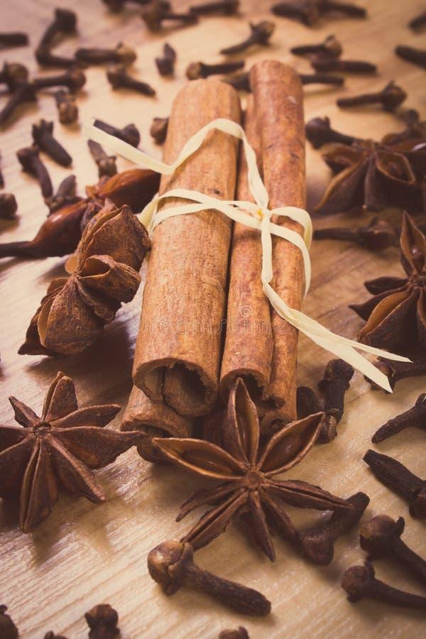 Винтажное фото, анисовка звезды, ручки циннамона и гвоздичные деревья на деревянном столе, приправляя для варить стоковые изображения