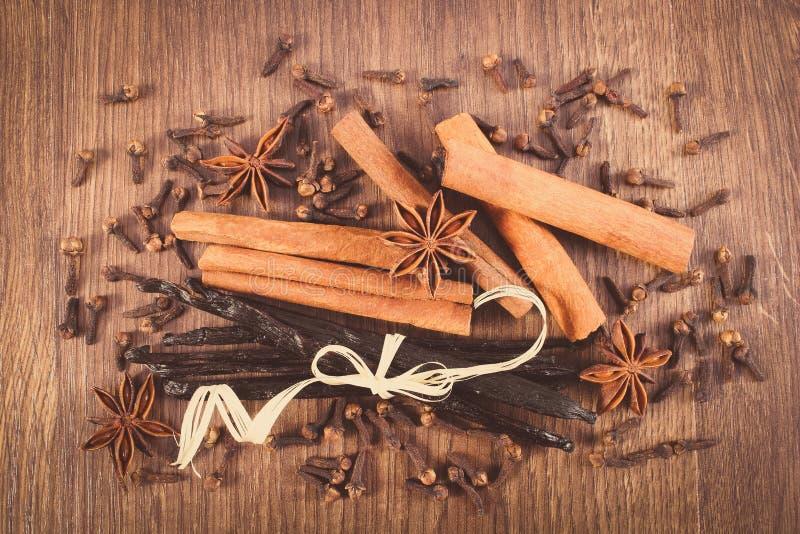 Винтажное фото, ваниль, ручки циннамона, анисовка звезды и гвоздичные деревья на деревянной поверхности стоковые изображения