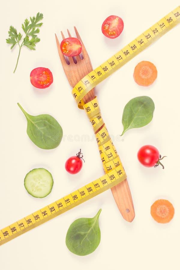 Винтажное фото, деревянная вилка обернуло рулетку и свежие зрелые овощи, концепцию уменьшения и здоровое питание стоковые фотографии rf