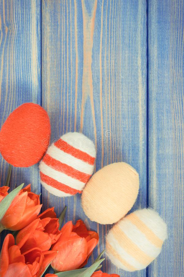 Винтажное фото, красные тюльпаны и пасхальные яйца обернули шерстяную строку, праздничное украшение, космос экземпляра для текста стоковые фото
