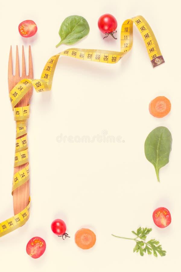 Винтажное фото, рамка деревянной вилки обернутая в рулетке и свежие зрелые овощи, концепция уменьшения стоковые фотографии rf