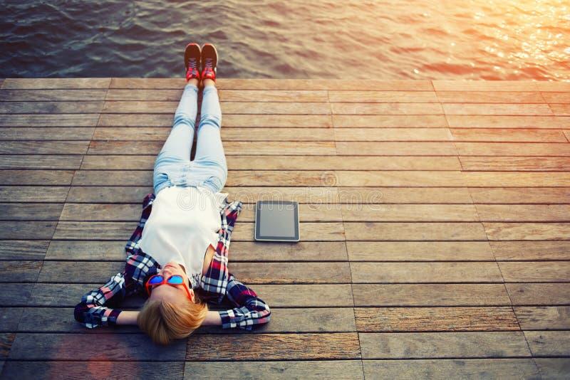 Винтажное фото расслабляющей молодой женщины в природе с таблеткой стоковые изображения