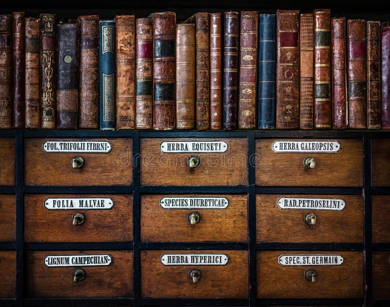 Винтажные, антикварные книги на деревянном старом фармацевтическом шкафе Ретро медицинская и фармацевтическая предпосылка Перевод стоковые фото