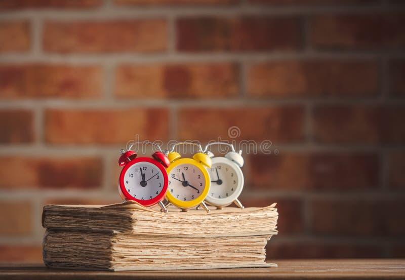 Винтажные будильники и старые книги стоковые изображения rf