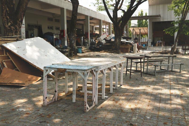 Винтажные деревенские деревянные табуретки стульев таблиц покрашенные в цветах Teal/белых в внешним покинутом гаражом JunkYard за стоковое изображение