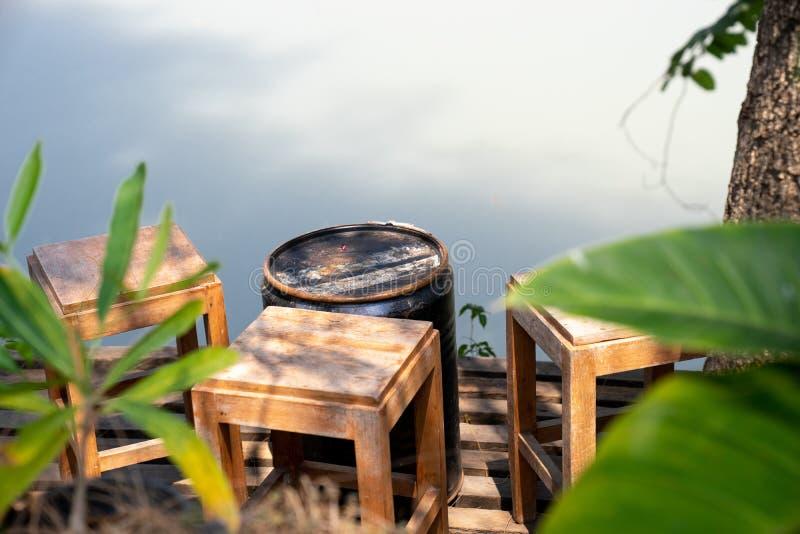 винтажные деревянные табуретки на деревянном балконе под деревом, смотрящ на реку со светом и тенью стоковое изображение