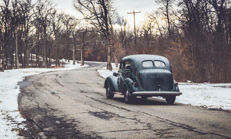 Винтажные зеленые классические приводы автомобиля вниз со старой извилистой дороги в зиме стоковые изображения