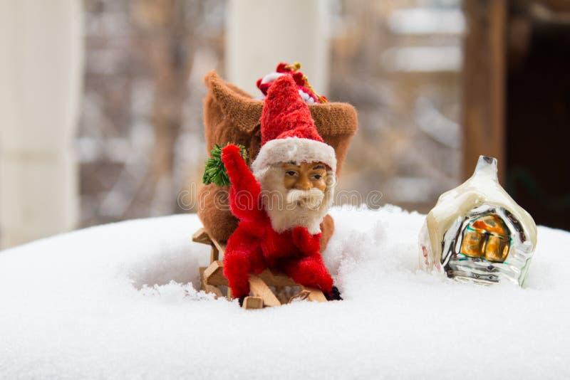 Винтажные игрушки рождества Гном на деревянных санях и покрытое снег стоковые изображения