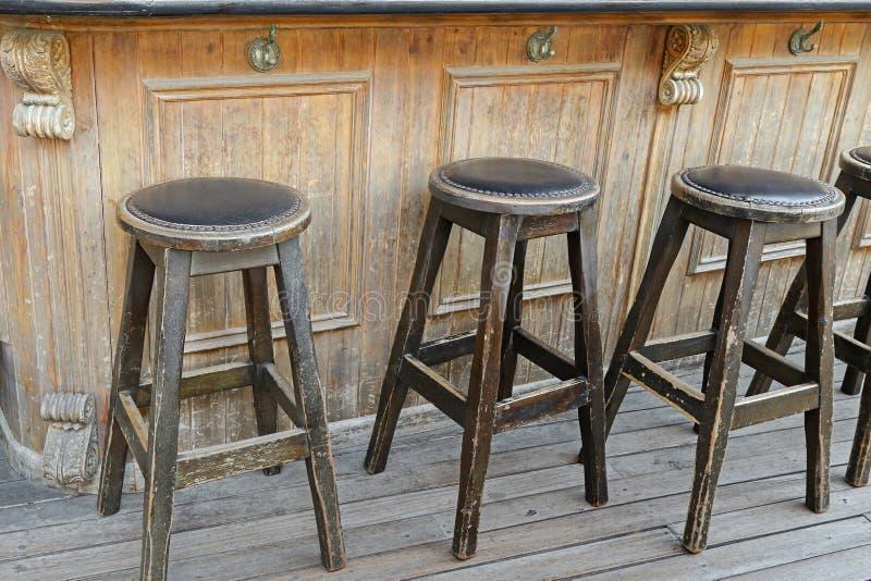 Винтажные и деревенские деревянные барные стулы на деревянном поле перед стоковые изображения