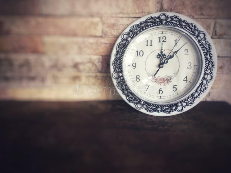 Винтажные классические часы на деревянном столе перед кирпичной стеной стоковое изображение