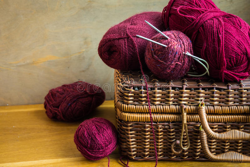 Винтажные клубоки красной пряжи шерстей, иглы на деревянной таблице, вязать, ремесла bolls плетеной корзины, хобби стоковая фотография rf