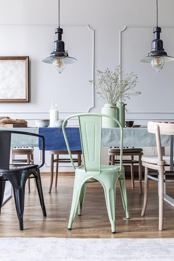 Винтажные лампы и зеленый стул на таблице в простом интерьере столовой Реальное фото стоковые фотографии rf