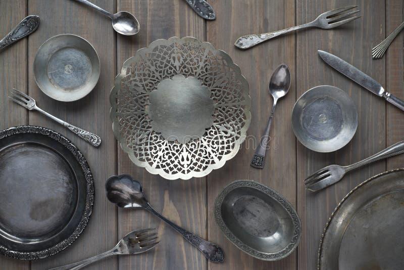 Винтажные ложки, вилки, ножи и металлические пластины на серой деревянной предпосылке стоковая фотография rf