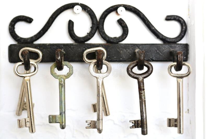 Винтажные металлические крюки вися старые ключи на белой предпосылке стоковая фотография rf