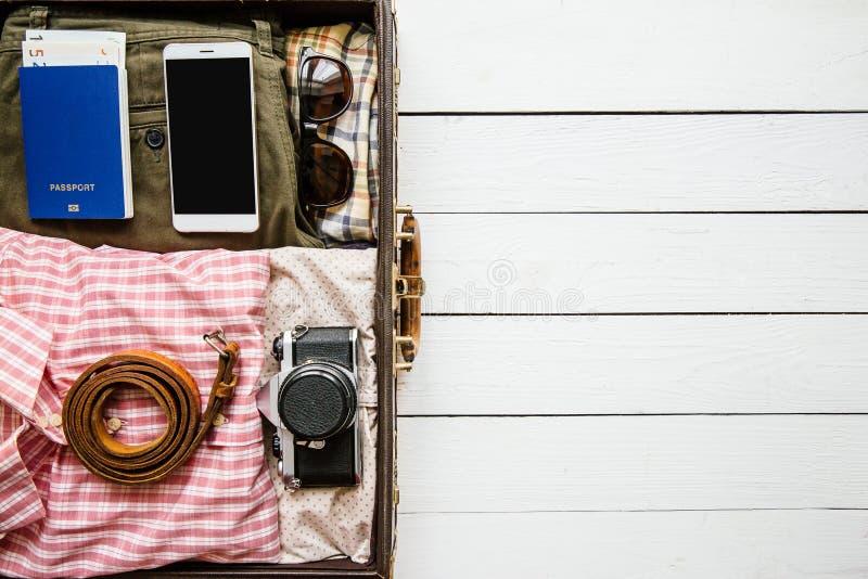 Винтажные одежды хипстера, ботинки, шляпа, смартфон, аксессуары упакованные в чемодане на белом деревянном столе перемещение карт стоковое изображение rf
