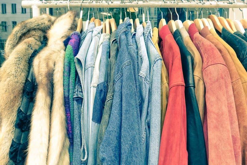 Винтажные подержанные одежды вися на магазине кладут на полку на блошинном стоковые фотографии rf