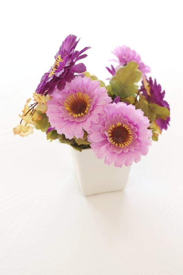 Винтажные розовые и фиолетовые искусственные цветки на белой ткани внутри стоковые изображения
