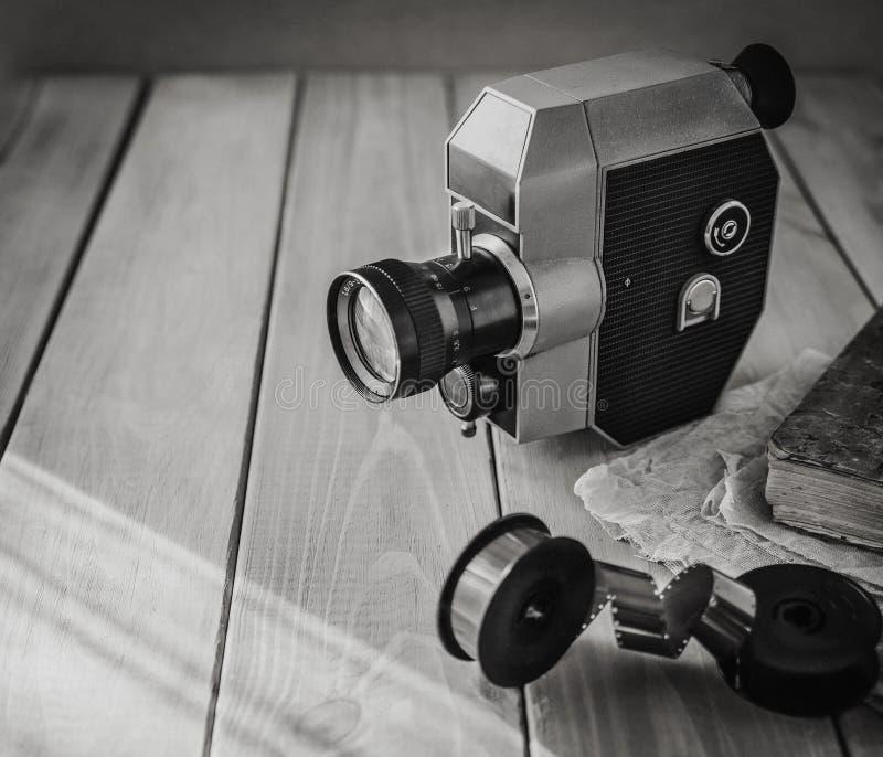Винтажные старые вьюрки киносъемочного аппарата и фильма на деревянном столе, старой книге, clothl фото ретро скопируйте космос стоковые изображения rf