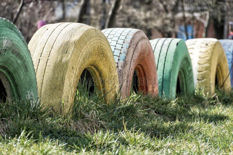 Винтажные шины для грузовых автомобилей, выкопанные в землю как огражд стоковые фото