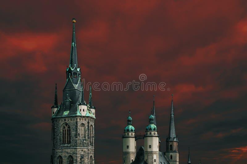 Винтажные spiers европейских церков на предпосылке красного голубого неба в городе здорового Заале, Германии стоковые фотографии rf