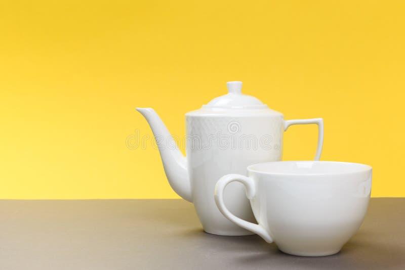 Винтажный белый чайник и чашка фарфора на серой доске и желтой предпосылке стоковые фото